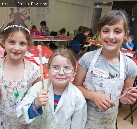 An image of three girls in white painting coats holding up paintbrushes