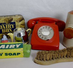 A red rotary dial phone along with old soap, kitchen items and scrubbing brush