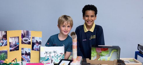 Two schoolchildren standing at a stall with their science project