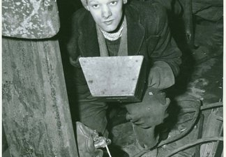 Worker at munitions factory holding a piece of equipment