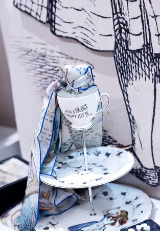 Image of a cake stand and scarf, both Alice in Wonderland themed