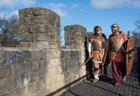 Two men dressed as Roman soldiers standing on a stone wall