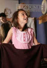 A young girl laughs while dressing up