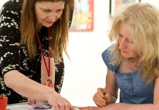 Tutor helping adult in art class