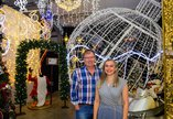 A man in a checked shirt and a woman in a patterned dress standing in front of large Christmas decorations with lots of twinkly fairy lights