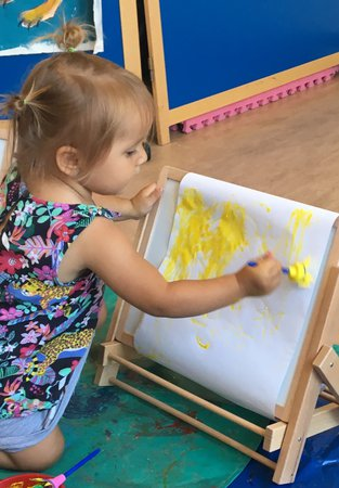 a toddler at an easel painting