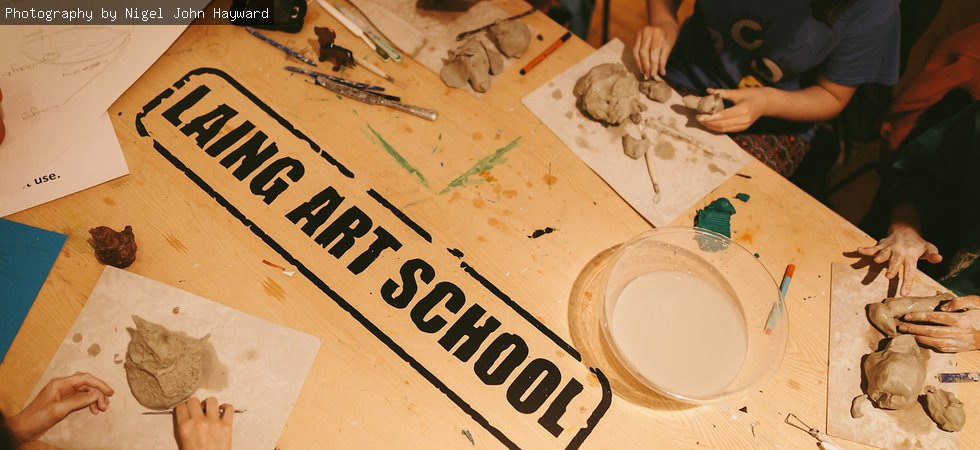 A photograph of a table with 'Laing Art School' printed on it