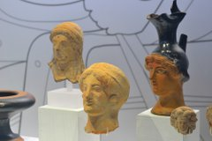 Four Ancient Greek artefacts showing feminine heads and faces. One item is a jug.