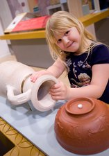 Child with three roman pottery handling objects