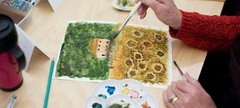 a photograph of a person painting a watercolour flower