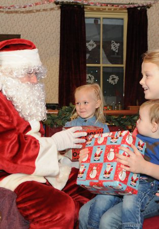 Santa meeting three children and giving them gifts