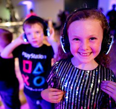 Children smiling with headphones on under disco lighting