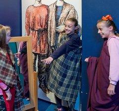 Three school age girls wearing Roman cloth drapes