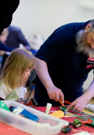A volunteer helping a young girl with an art project