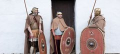 three Roman soldiers stand in front of the reconstructed Barrack Block