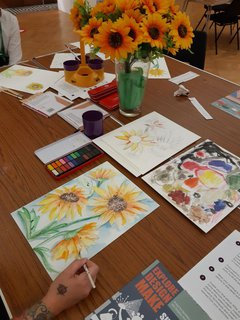 people doing watercolour painting round a table