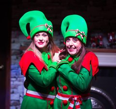 Two people dressed up as Christmas elves in red and green