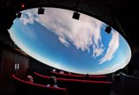 Visitors look up at a domed planetarium show. They are seeing clouds moving across a daylight sky