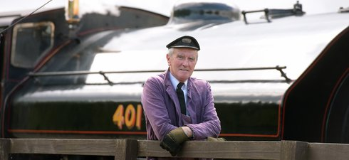 Man with cap in front of black steam locomotive