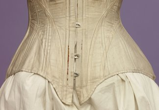 A pale pink Victorian corset on a mannequin