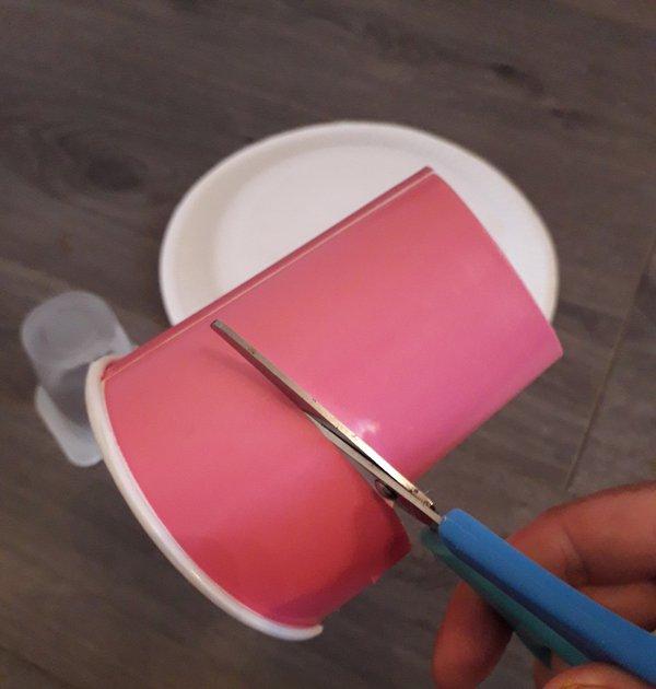Scissors cutting paper cup
