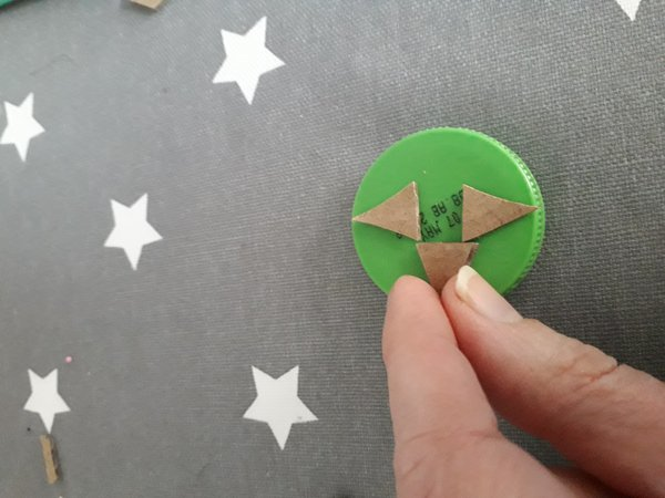 Cardboard shapes stuck to green bottle top