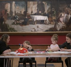 4 people sitting under tintoretto with crafts on their table