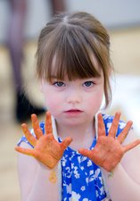 A young girl with paint on her hands