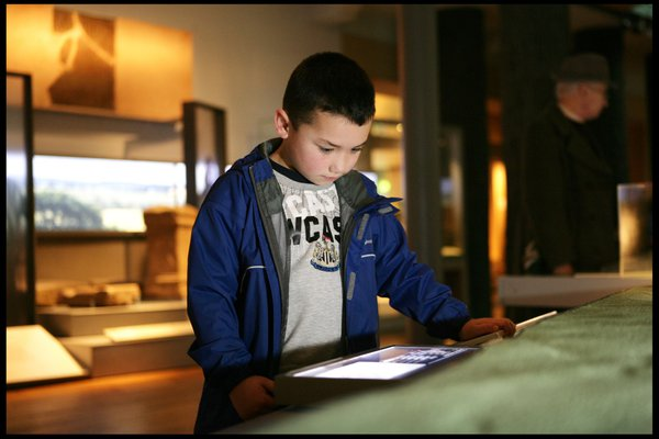 A young boy wearing a Newcastle United FC t-shirt looks at an interactive touchscreen at the Great North Museum