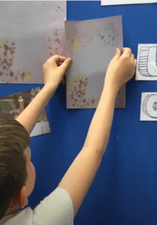 A child sticking artwork to a wall.
