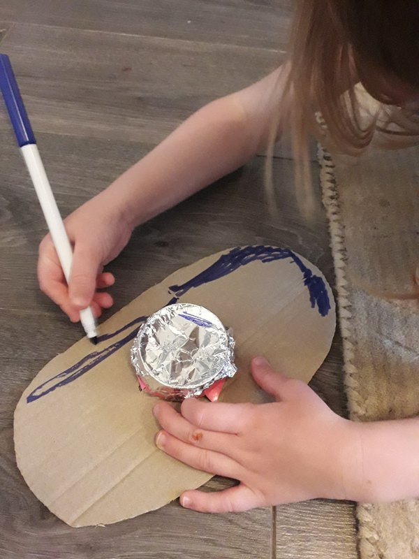 Child decorating cardboard shield using colouring pen