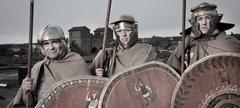 three men dressed as Roman infantry