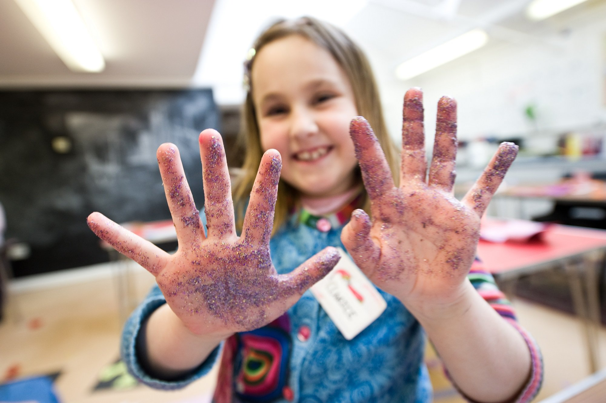 A girl with glitter on her hands shows them to the camera