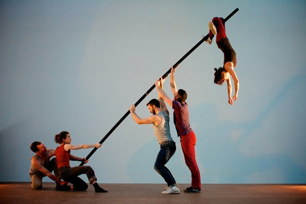 A choreographed scene with four dancers supporting a diagonal pole while a fifth dancer hangs upside down from the pole by the legs