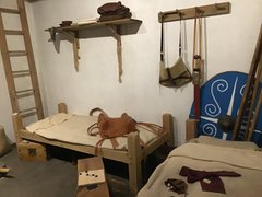 Reconstruction of cavalry barrack room with bed and Roman weapons