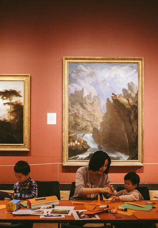 A family enjoying Big Wednesday activities with a John Martin painting in the background