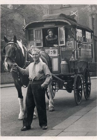 Black and white photo of man and women with their caravan and horse on the road, 1950