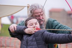 Historical man shows boy how to use bow