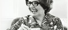 Dame Catherine Cookson laughs holding a cup of tea