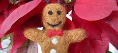 photo of a gingerbread man decoration hanging off a house plant. It is made from felted wool