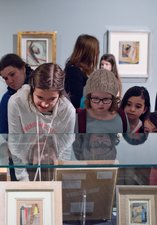A group of children viewing an art exhibition with Hatton Learning Officer, Hazel