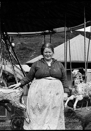 Black and white photo of a woman in front of a carousel.