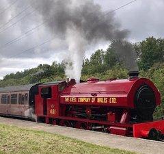 Red steam locomotive by platform