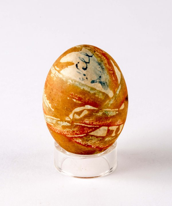 Decorated hen's egg, painted with orange and green patterns.