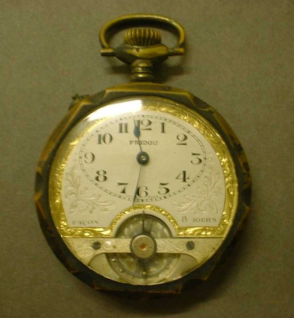 This is a pocket watch has a cream face with gilt decoration and black numbers.