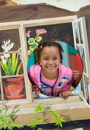 A girl playing in the toy house in the under fives area