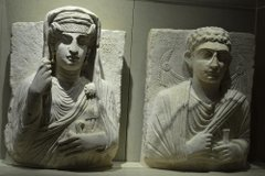Two finely carved stone artefacts showing human figures. They are both shown wearing draped fabrics