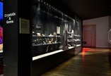 A glass museum case full of different crystals and gemstones