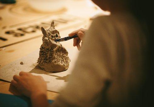 Girl making a clay panda sculpture