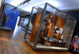 View of ethnographic items in glass museum cases. There are headdresses, statuettes and suits of armour